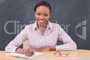Smiling teacher writing