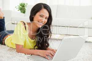Portrait of a beaming Latin woman using a laptop
