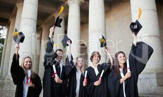 Smiling graduates holding up their hats