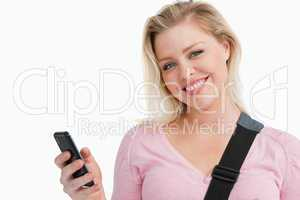 Blonde woman holding her mobile phone while writing a text