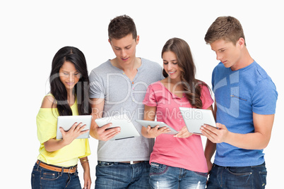 Four friends looking at their tablets and smiling