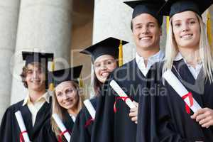 Close-up of five graduates posing