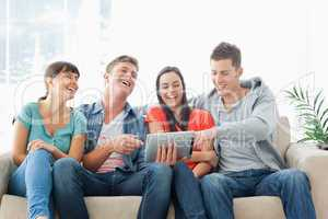 A laughing group of friends watch the tablet pc