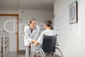 Patient sitting on a wheelchair in front of a doctor