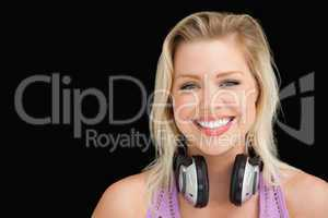 Happy blonde woman standing upright with headphones