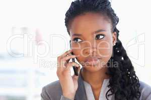 Young earnest employee talking on the phone in front of a bright