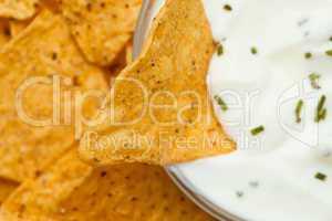 Close up of a nacho dipped into a bowl of dip