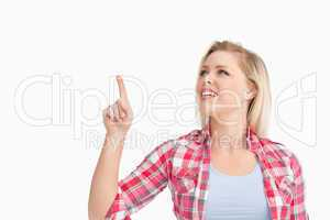 Blonde woman smiling while pointing her finger up