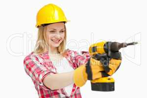 Joyful woman using an electric screwdriver