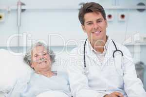 Doctor sitting on the bed next to a patient