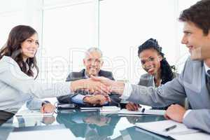 Two young executives shaking hands in front of their director an