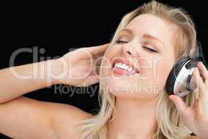 Joyful blonde woman listening to music through headphones