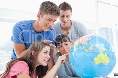 Students pointing to places in the world on a globe