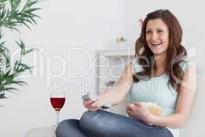 Woman smiling while pressing a remote control