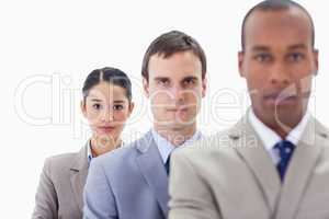 Big close-up of serious colleagues in a single line looking stra