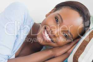 Black woman smiling while lying on side