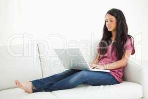 Unsmiling Latino student sitting on a sofa