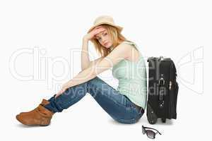 bored woman sitting near a suitcase