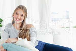 Smiling girl lying on the couch looking at the camera