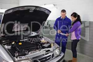 Mechanic holding a clipboard next to a woman