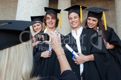 Close-up of a blonde graduate taking a picture of her friend