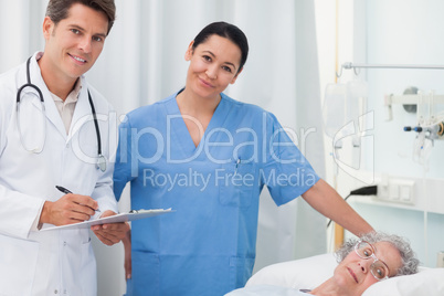 Doctor and nurse looking at camera next to a patient lying