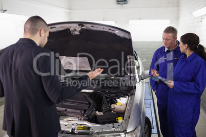 Client looking at a car next to mechanics