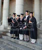 Laughing graduates posing the thumb-up