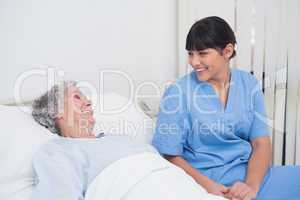 Nurse smiling to an elderly patient