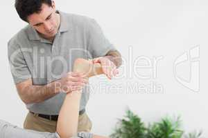 Brown-haired therapist stretching the foot of a patient