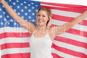 Joyful blonde woman holding the Stars and Stripes flag