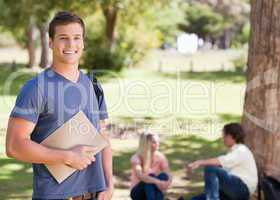 Portrait of a smiling student holding a textbook
