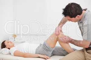 Brown-haired man massaging the knee of a woman