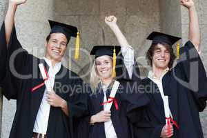 Graduates holding their diploma while raising arm