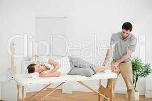 Woman lying on her side while being massaged by a man