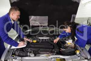 Mechanics checking a car engine