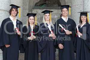 Smiling graduates posing