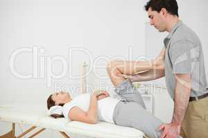 Osteopath stretching the leg of his patient
