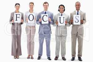 Happy business team holding the letters of FOCUS