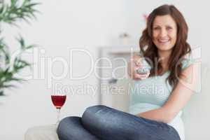 Woman pressing a remote control while sitting on a sofa