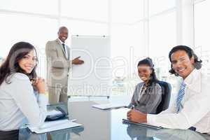 Smiling executive showing a flipchart while his colleagues are l