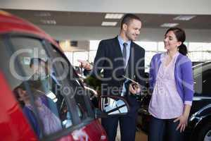 Salesman showing a car to a woman