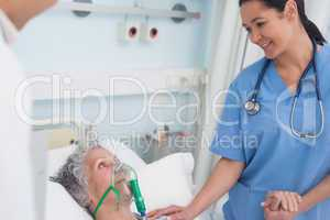 Nurse touching the hand of a patient