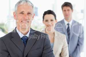 Mature manager followed by two young business people