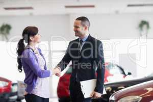 Smiling salesman shaking the hand of a woman
