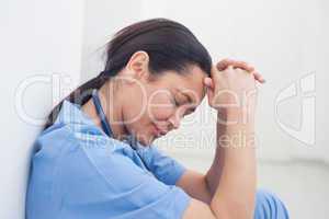 Upset nurse sitting on the floor