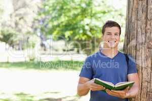 Portrait of a smiling toothy student holding a textbook