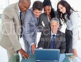 Four business people attentively listening to their mature manag