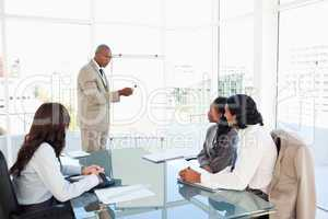Businessman pointing to something on the flipchart to explain th