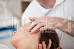 Doctor manipulating the side of the head of his patient